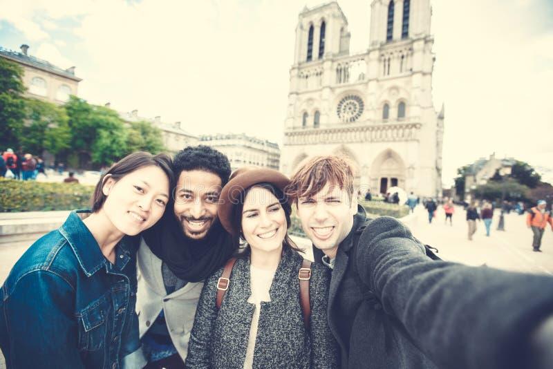 grupo Multi-étnico de amigos que têm o divertimento em Paris, Notre Dame imagem de stock