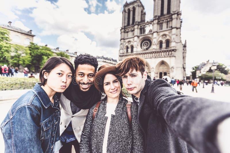 grupo Multi-étnico de amigos que têm o divertimento em Paris, Notre Dame fotos de stock royalty free