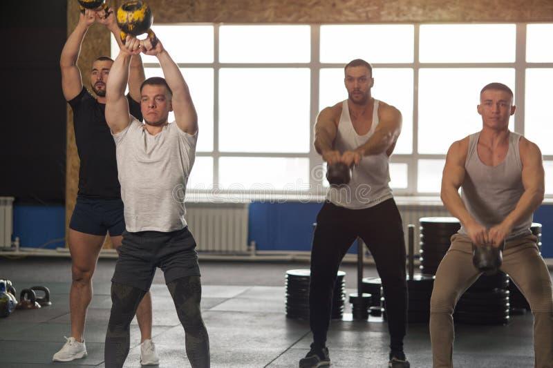 grupo Multi-étnico de atletas de sexo masculino que entrenan con Kettlebells en gimnasio fotografía de archivo