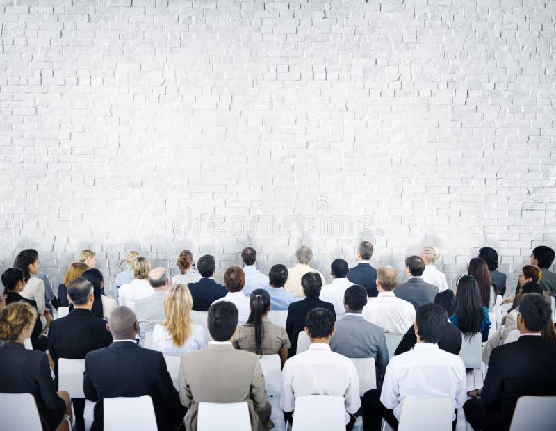 Grupo multi-étnico de audiências com parede de tijolo imagens de stock
