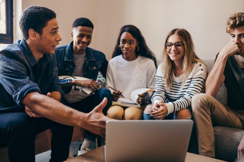 grupo Multi-étnico de estudiantes con el ordenador portátil en campus imágenes de archivo libres de regalías