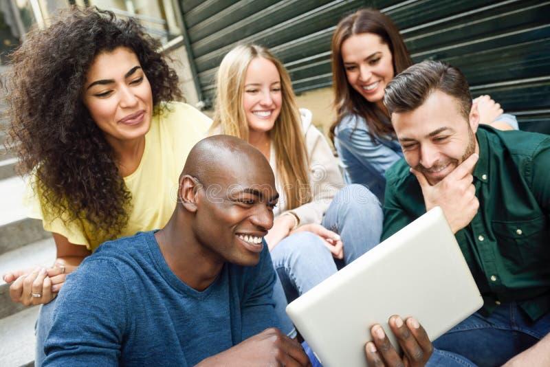 grupo Multi-étnico de gente joven que mira una tableta fotos de archivo
