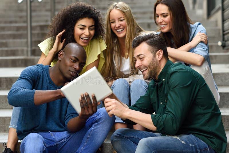grupo Multi-étnico de gente joven que mira una tableta fotos de archivo libres de regalías