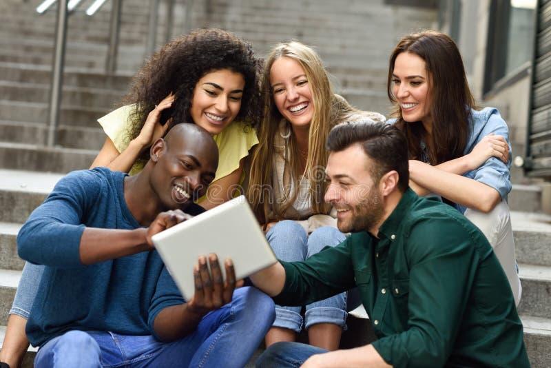 grupo Multi-étnico de gente joven que mira una tableta foto de archivo