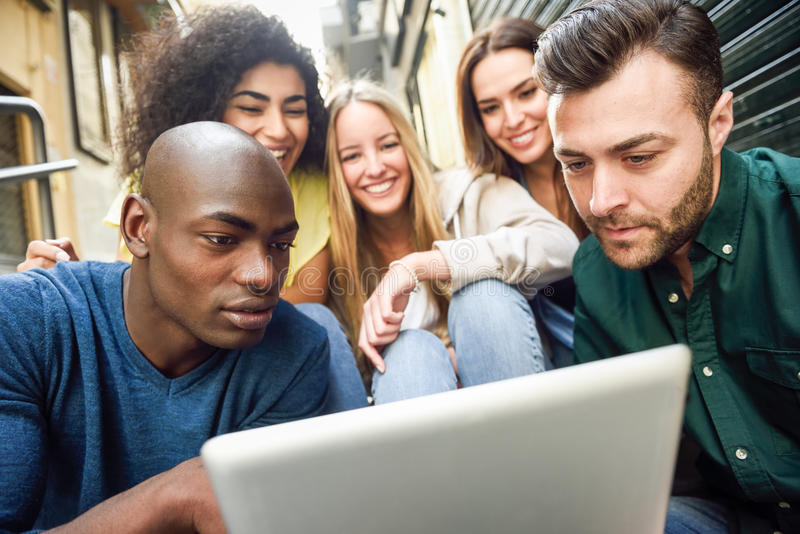 grupo Multi-étnico de gente joven que mira una tableta fotografía de archivo