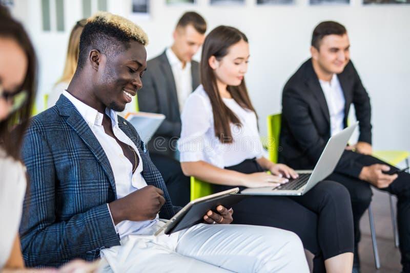 grupo Multi-étnico de la gente de la oficina usando los artilugios en la reunión del equipo, ejecutivos serios que trabajan en lo fotografía de archivo libre de regalías
