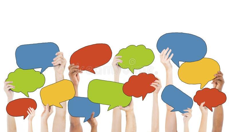 Grupo Multi-étnico de manos que llevan a cabo burbujas del discurso ilustración del vector
