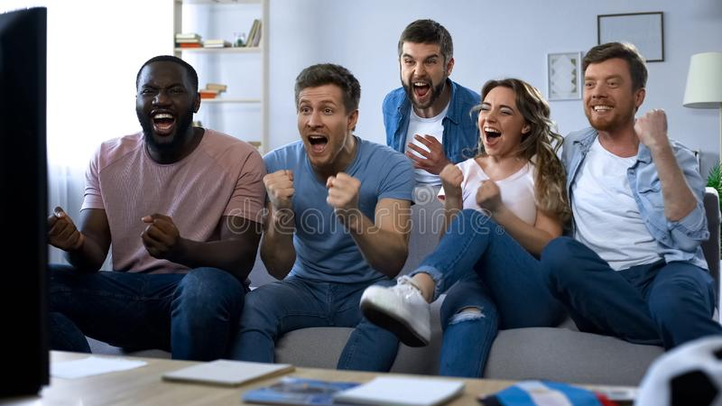 grupo Multi-étnico de partido de fútbol de observación de los amigos en casa, celebrando meta imagen de archivo