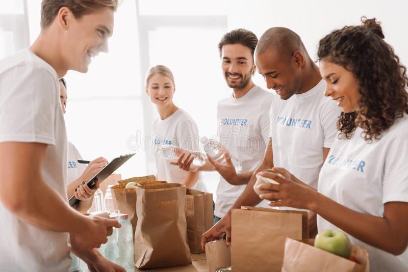 grupo multi-étnico novo de voluntários que põem o alimento e as bebidas em uns sacos de papel imagem de stock