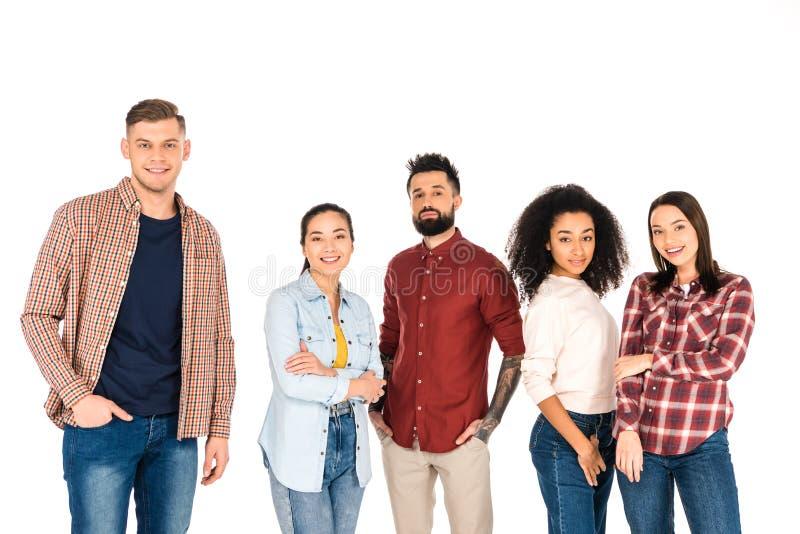 grupo multicultural alegre de gente joven que se coloca con los brazos y las manos cruzados en los bolsillos aislados imagen de archivo libre de regalías