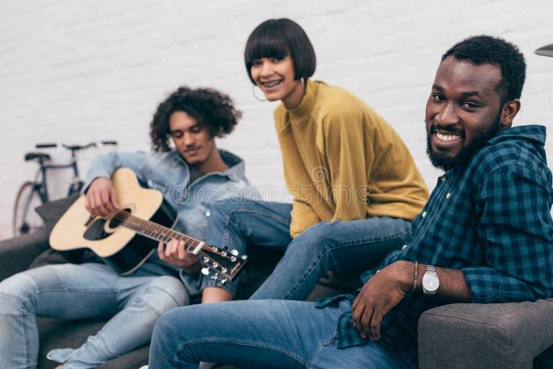 grupo multicultural de amigos que se sientan en el sofá y jugar fotos de archivo libres de regalías