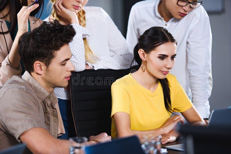grupo multicultural de colegas del negocio que miran la presentación en el ordenador portátil en moderno foto de archivo
