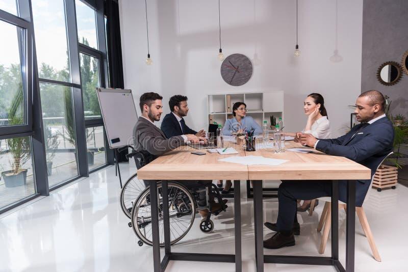 grupo multicultural de empresários que discutem a ideia nova ao sentar-se na tabela imagens de stock