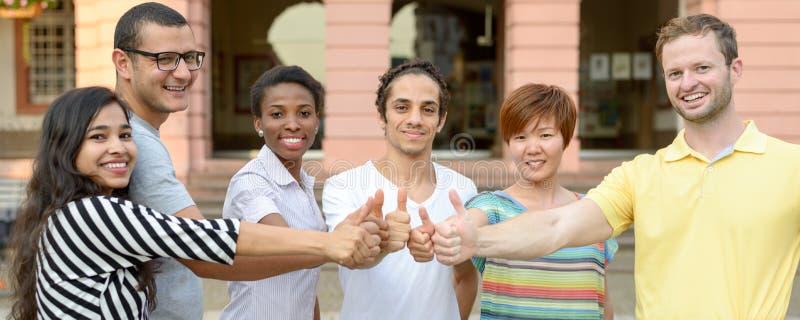 Grupo multicultural de estudiantes que dan los pulgares para arriba imagenes de archivo