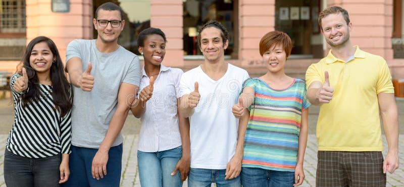 Grupo multicultural de estudiantes que dan los pulgares para arriba fotos de archivo libres de regalías