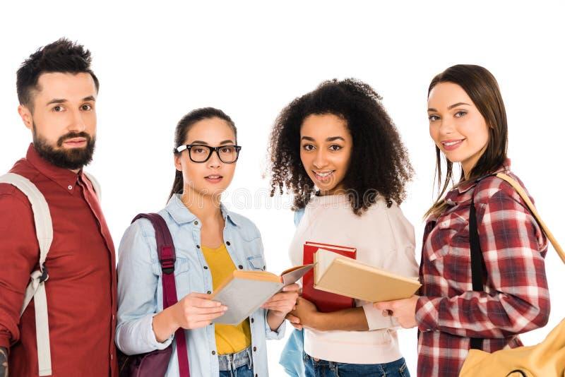 grupo multicultural de gente joven que se coloca con los libros aislados foto de archivo libre de regalías