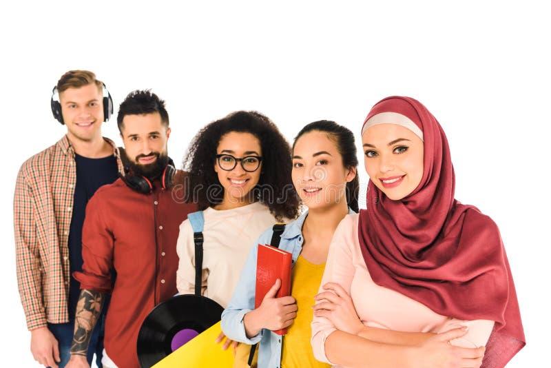 grupo multicultural de gente joven que se coloca y que sonríe aislada imágenes de archivo libres de regalías