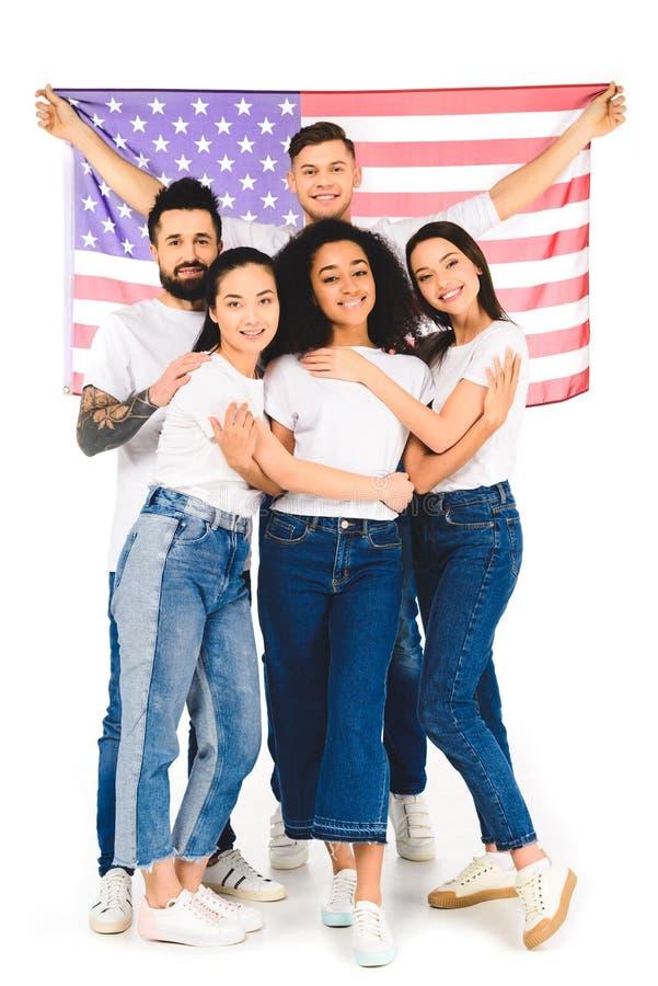 grupo multicultural de gente joven que sonríe y que abraza mientras que sostiene la bandera de los E.E.U.U. aislada fotos de archivo libres de regalías
