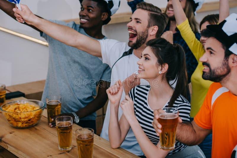 grupo multicultural entusiasmado de amigos em chapéus da bola de futebol que comemoram e que olham o fósforo de futebol foto de stock