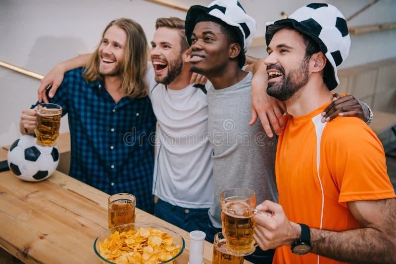 grupo multicultural entusiasmado dos fan de futebol masculinos nos chapéus da bola de futebol que guardam a cerveja e que olham o imagem de stock