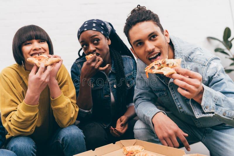 grupo multicultural sonriente de amigos que comen la pizza imagen de archivo libre de regalías