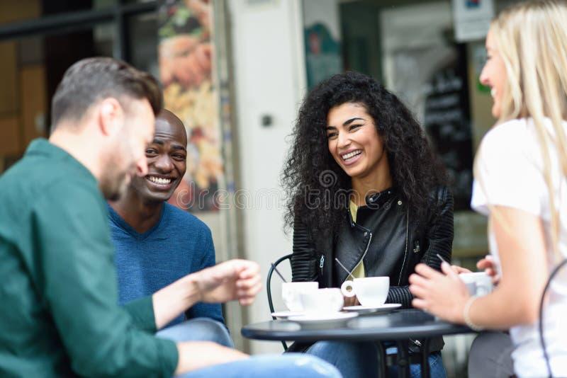 Grupo multidisciplinar de quatro amigos tomando um café juntos fotos de stock royalty free