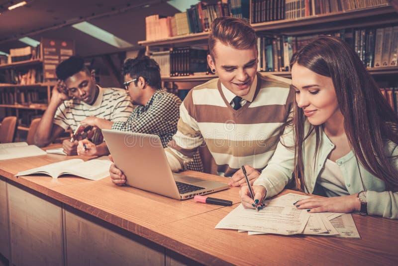 Grupo multinacional de estudiantes alegres que estudian en la biblioteca de universidad fotografía de archivo