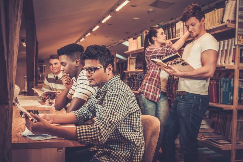 Grupo multinacional de estudiantes alegres que estudian en la biblioteca de universidad imagen de archivo libre de regalías