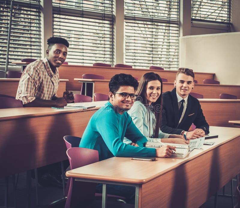 Grupo multinacional de estudiantes alegres que toman una parte activa en una lección mientras que se sienta en una sala de confer foto de archivo libre de regalías