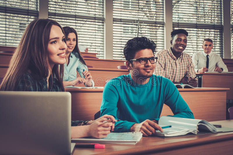 Grupo multinacional de estudiantes alegres que toman una parte activa en una lección mientras que se sienta en una sala de confer imágenes de archivo libres de regalías