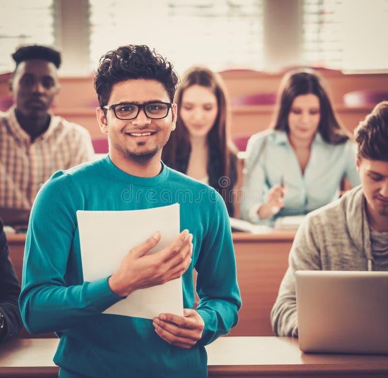 Grupo multinacional de estudiantes alegres que toman una parte activa en una lección mientras que se sienta en una sala de confer imagen de archivo