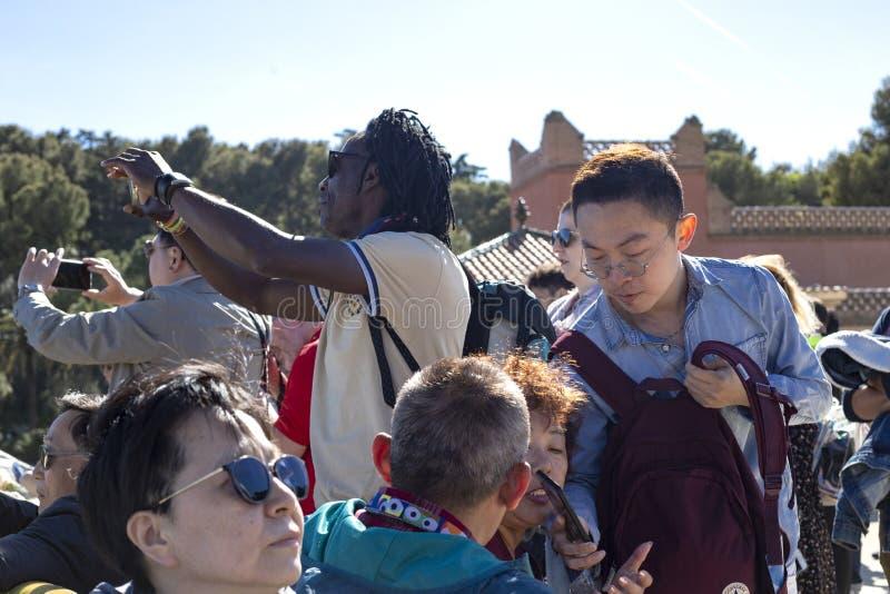 Grupo multinacional de turistas de los países diferentes en el parque Guell, Barcelona, Cataluña, España 2019-05-01 imagenes de archivo