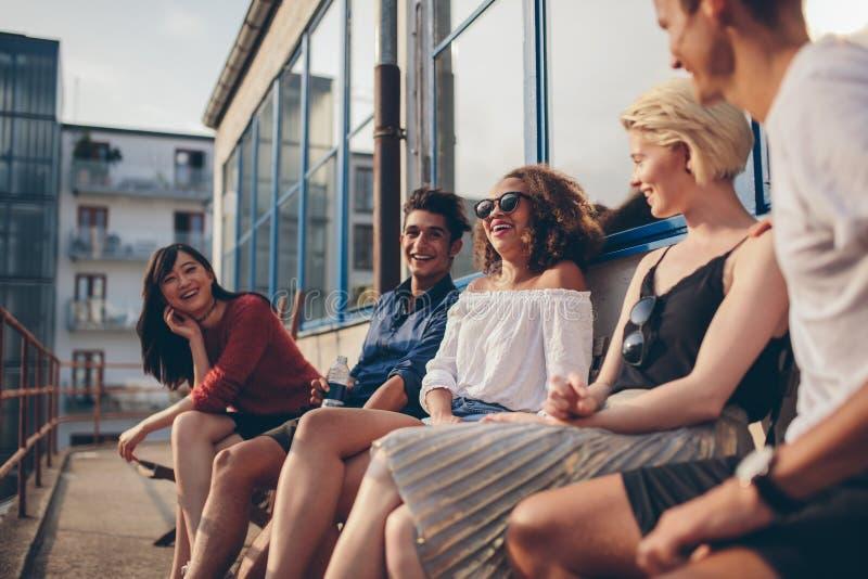 Grupo multirracial de amigos que se sientan en balcón y la sonrisa imagenes de archivo