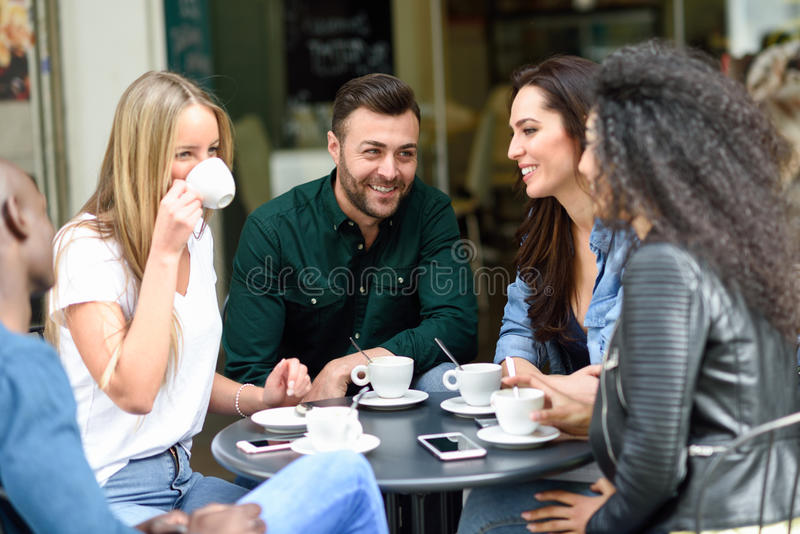 Grupo multirracial de cinco amigos que comem um café junto imagens de stock royalty free