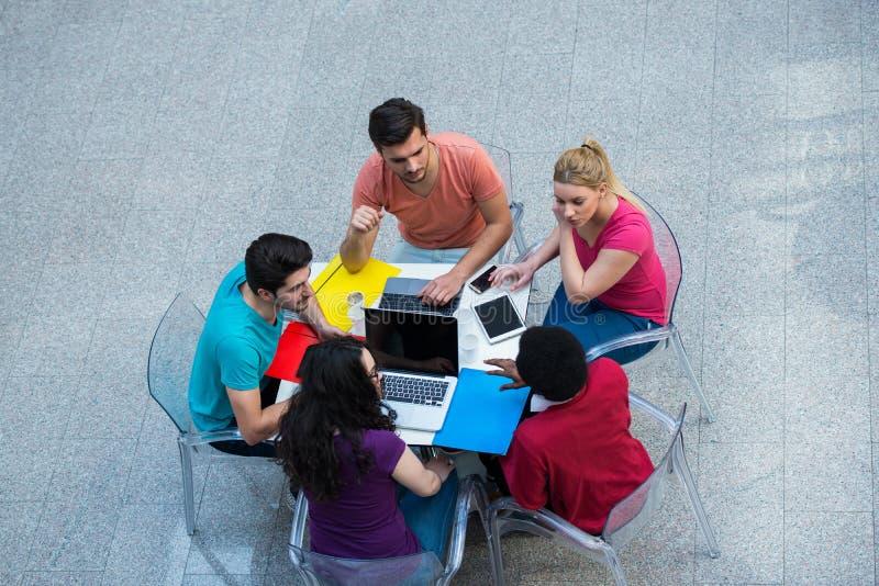Grupo multirracial de estudiantes jovenes que estudian junto Tiro de alto ángulo de la gente joven que se sienta en la tabla fotos de archivo