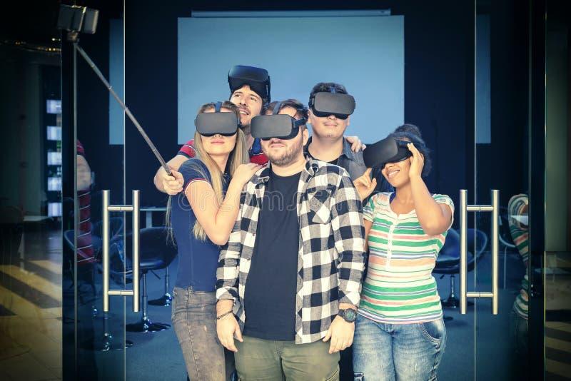 Grupo multirracial feliz de los amigos que toma el selfie que juega los vidrios del vr interiores foto de archivo