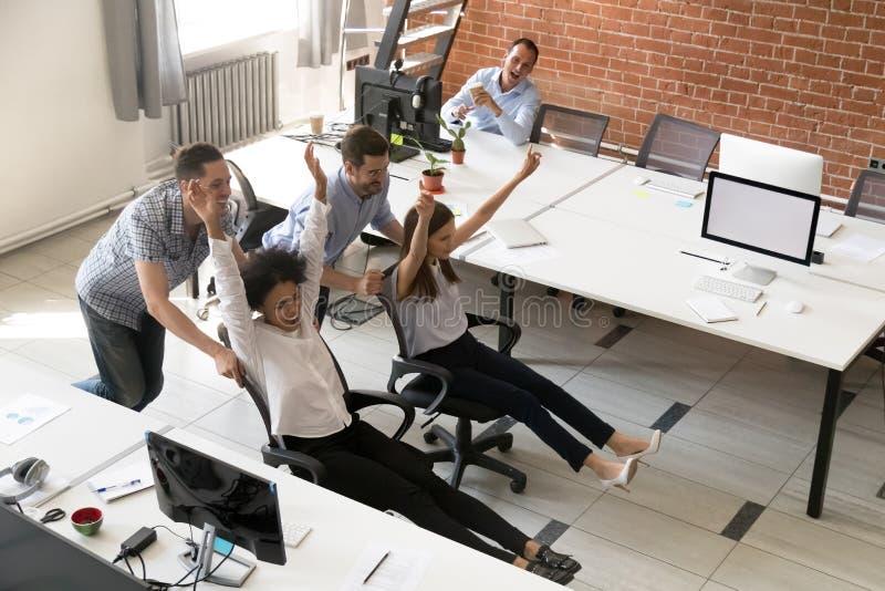 Grupo multirracial feliz de los colegas que se divierte junto en oficina foto de archivo