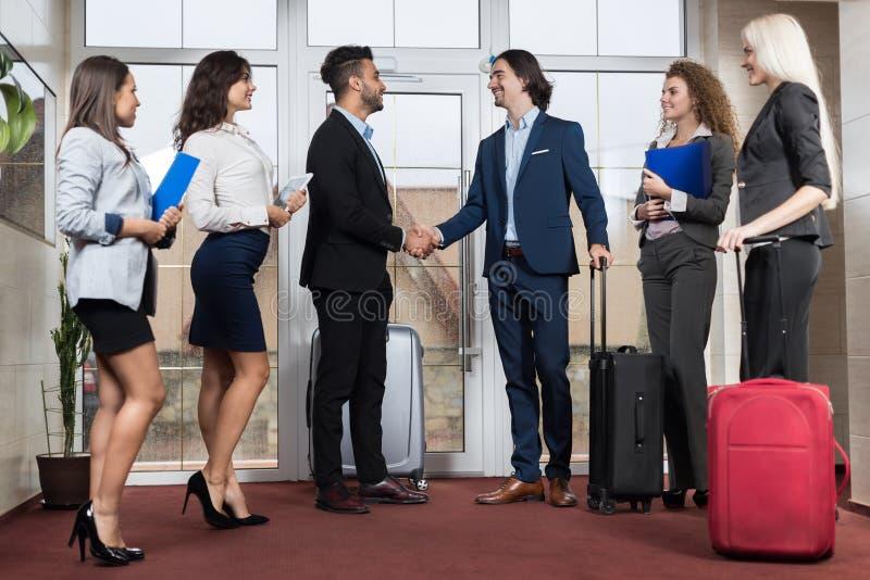 Grupo na entrada, dois homem de negócios Meeting Handshake de Meeting Business People do recepcionista do hotel imagens de stock royalty free