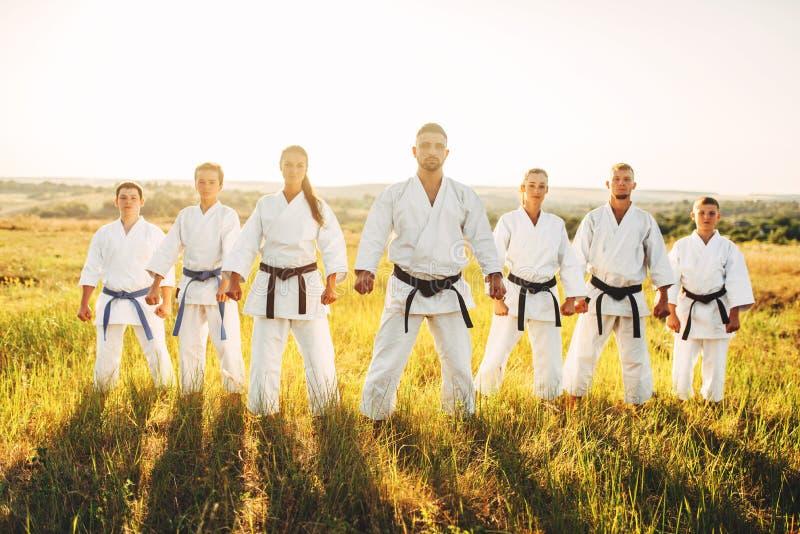 Grupo no quimono branco, exercício do karaté no campo fotos de stock royalty free