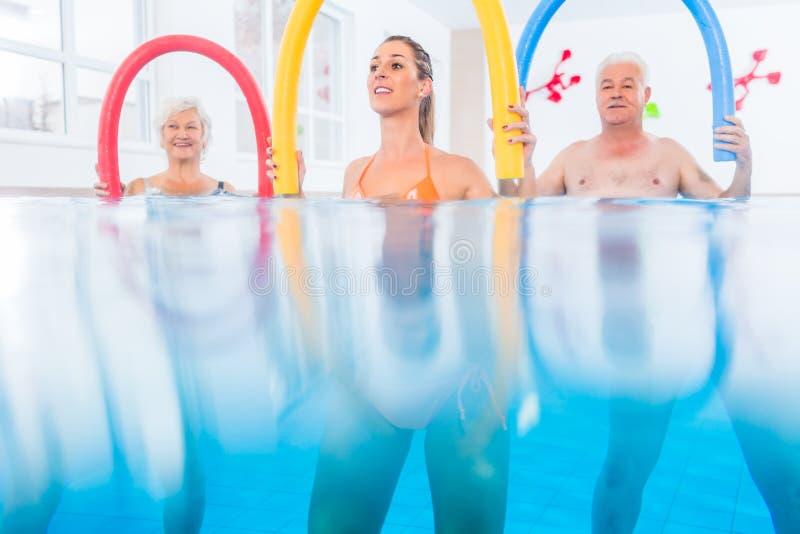Grupo no treinamento da fisioterapia da água foto de stock