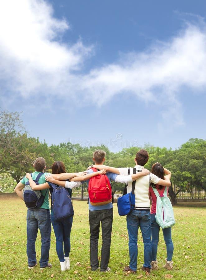 grupo novo de estudantes que olham o céu imagens de stock