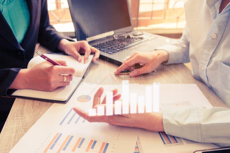 Grupo novo dos gestores de conta que trabalha e que discute dados financeiros do gráfico do plano no escritório fotos de stock