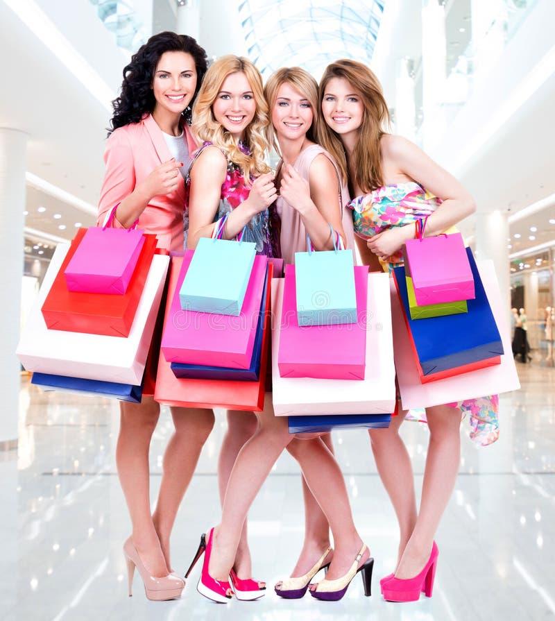 Grupo novo feliz de mulheres após a compra na alameda grande fotografia de stock