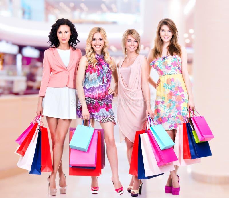 Grupo novo feliz de mulheres após a compra na alameda grande imagem de stock