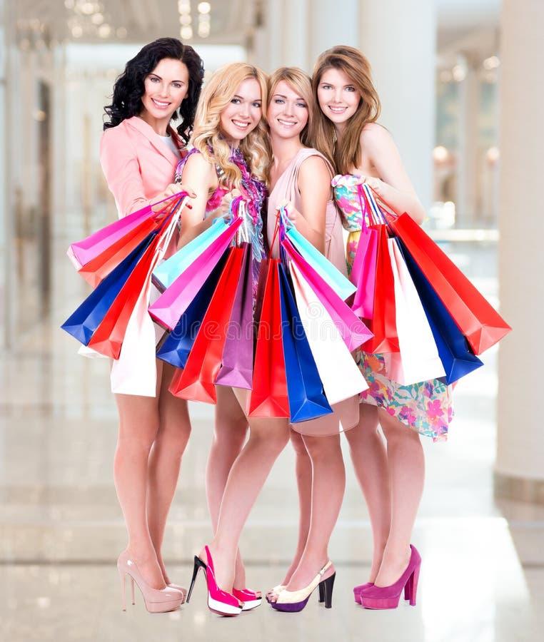 Grupo novo feliz de mulheres após a compra na alameda grande imagens de stock