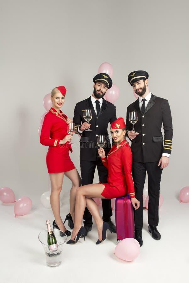 Grupo novo feliz de pilotos e de comissárias de bordo imagens de stock royalty free