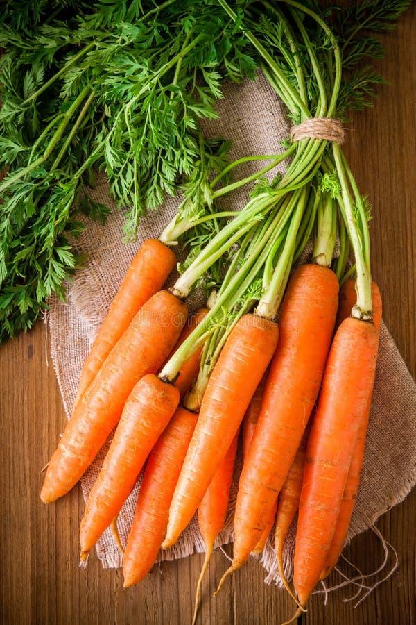 Grupo orgânico fresco das cenouras no fundo de madeira foto de stock royalty free