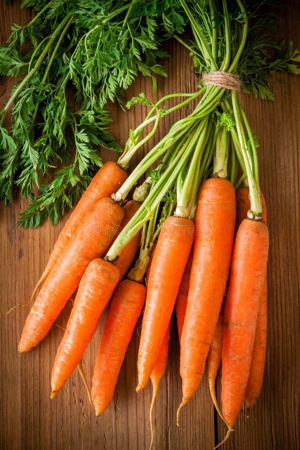 Grupo orgânico fresco das cenouras no fundo de madeira imagens de stock