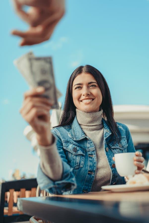 grupo outstretching da jovem mulher dos dólares à disposição ao garçom fotografia de stock royalty free
