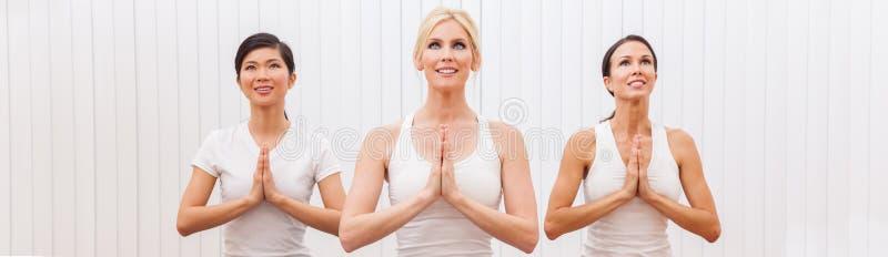 Grupo panorâmico de três mulheres bonitas que praticam a ioga fotografia de stock